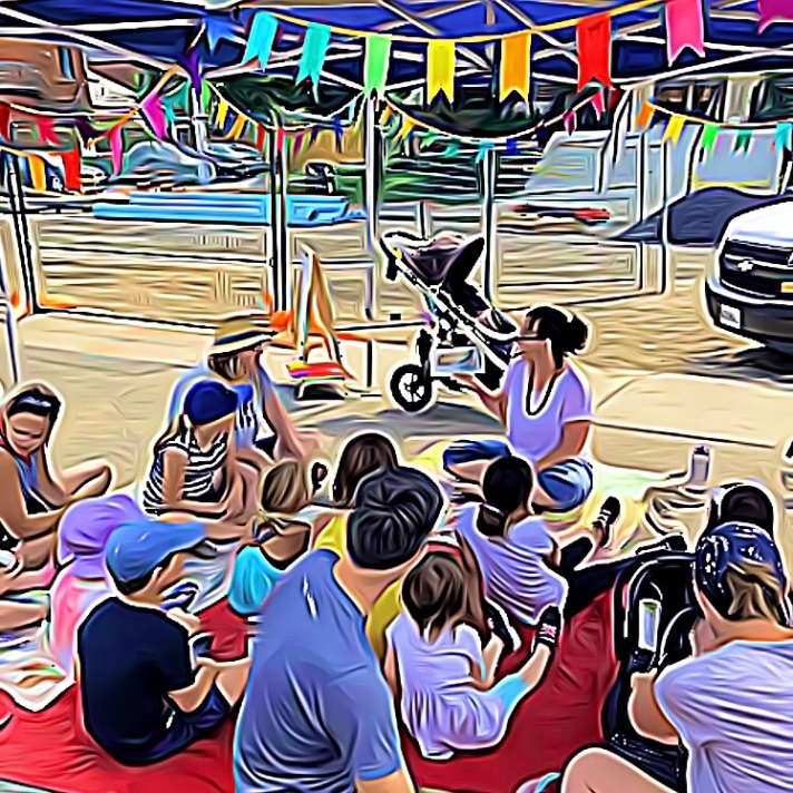 Image: an animated version of a photograph taken at Locke Street Farmer's Market. Amber reads a picture book to gathered families.