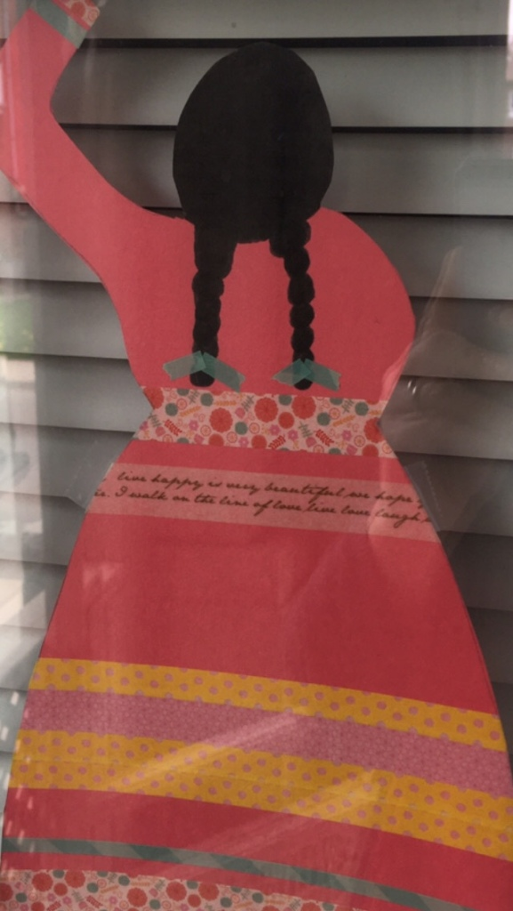 A red construction paper dress with stripes in a window to raise awareness for Missing and Murdered Women, Girls, and 2-Spirit People.
