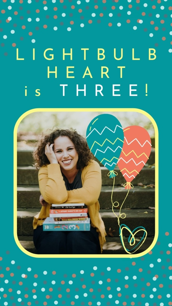 "Yellow text against a turquoise background with dotted confetti reads ""Lightbulb Heart is three!"" An inset photo of Amber, a smiling white woman with curly hair wearing a yellow cardigan, who leans her head on her hand and elbows on a stack of children's books. She sits on park steps and  is crowded by turquoise and coral cartoon balloons."
