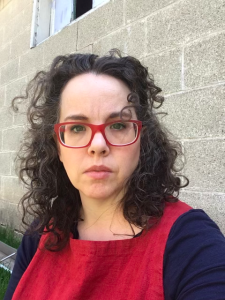 Amber, a white woman with dark curly hair sits in front of a cinderblock wall. She wears red glasses and a red apron over a navy tee shirt.